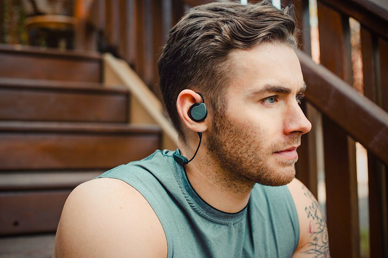 Guy sitting on stairs using Versafit Wireless headphones